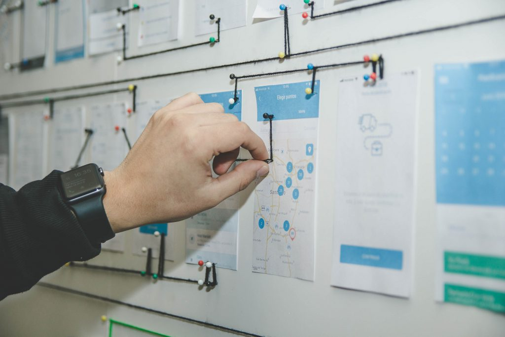 a man is planning mobile app flow on the wall board