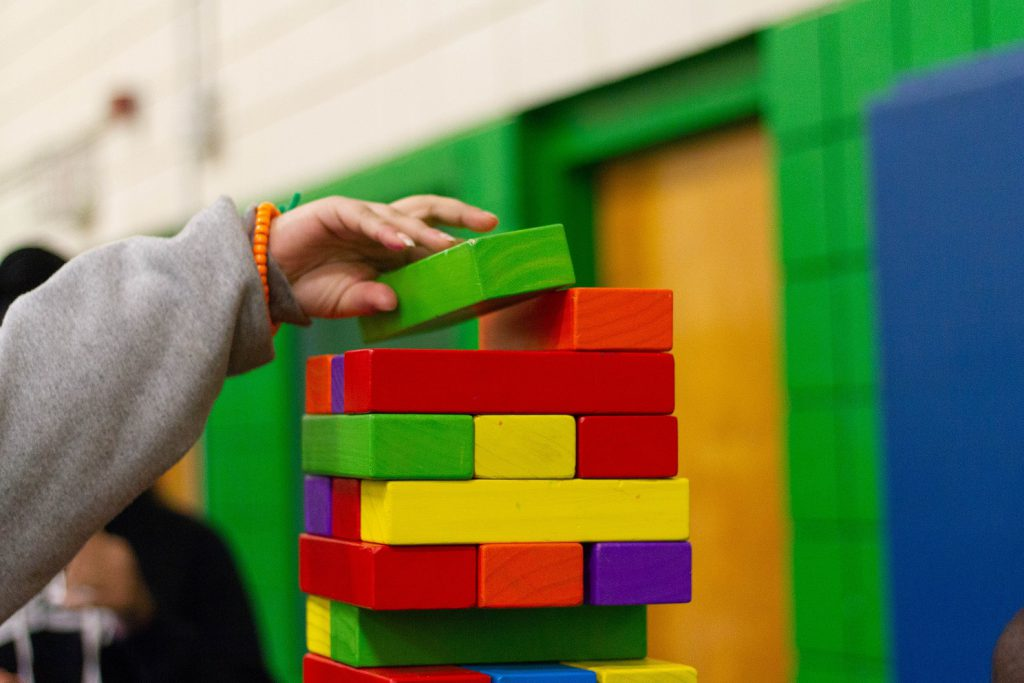child is building a tower from the color blocks