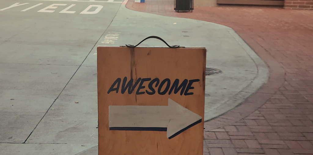 """a sign with """"awesome"""" letters and an arrow"""