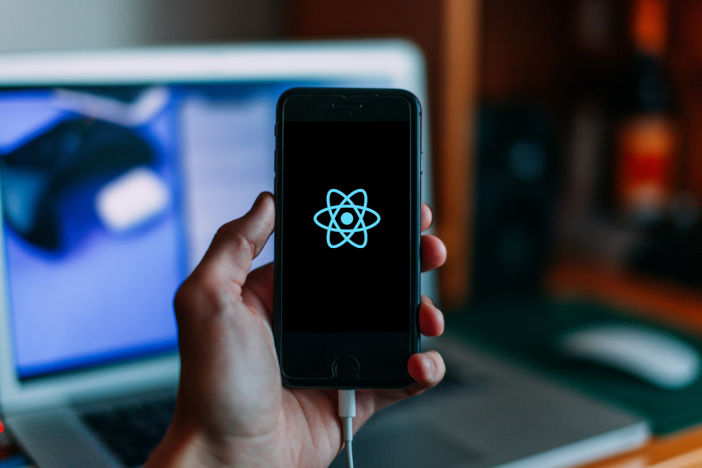 a hand holding smartphone with react native logo on it