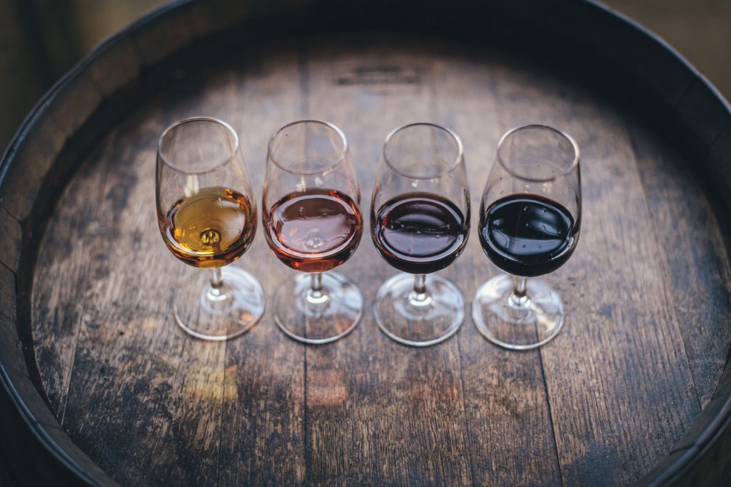 four glasses of a different wine on the barrel