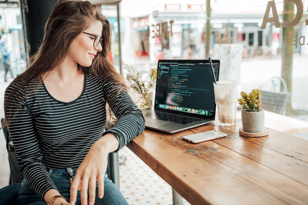 a female developer next to laptop with coffee on a table